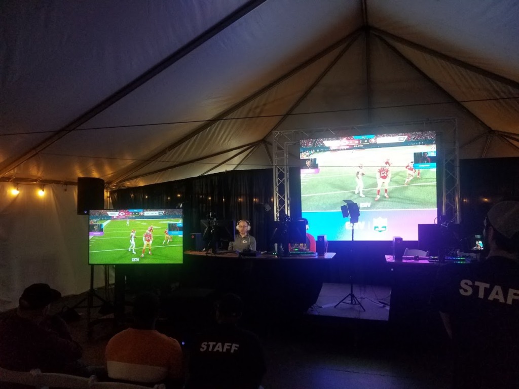 Two large screens show video game play during a gaming event inside a large tent.